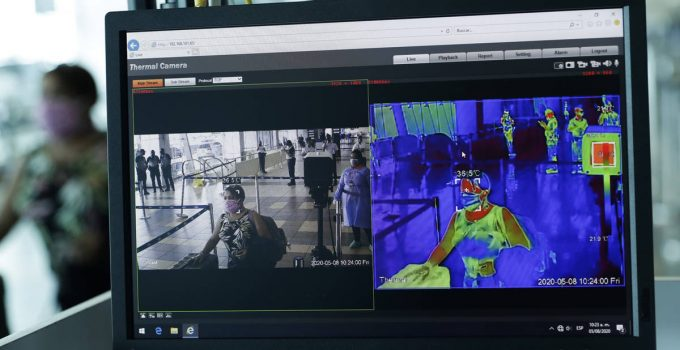 A thermal camera monitor shows the body temperature of a passenger on her way to boarding a hum ...