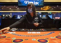 A Blackjack dealer wears a mask while she deals a game at Palace Station as casinos have reopen ...
