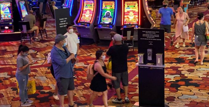 A group of patrons at the New York-New York wear masks on the casino floor near a hand sanitize ...