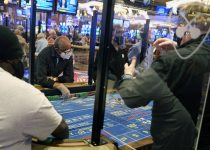 Partitions between players and face masks allow gamblers to enjoy craps at the Hard Rock Casino ...